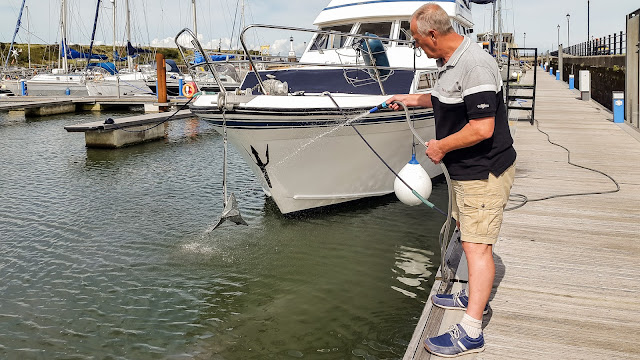 Photo washing the anchor after we tested it by dropping it in the marina