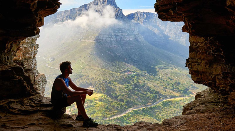 Rapaz sentado na porta de uma caverna contemplando as montanhas ao redor na paisagem