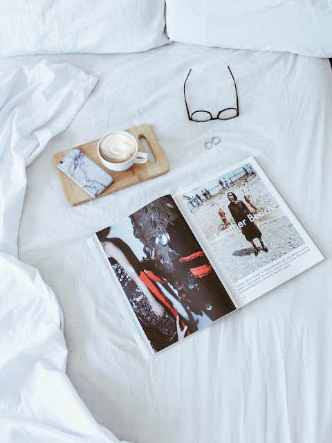 Bed with the covers back showing a tray with phone and coffee on a tray, glasses and a magazine laid out