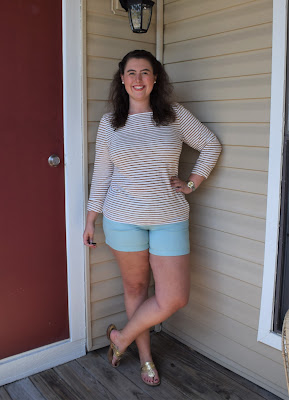 a woman wearing a gold striped tee, turquoise shorts, gold sandals, and a gold watch