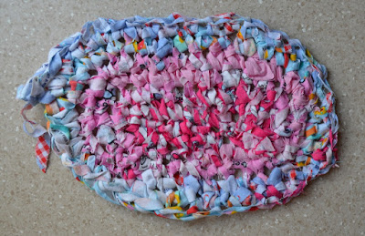 A partially completed oval-shaped crocheted rag rug.