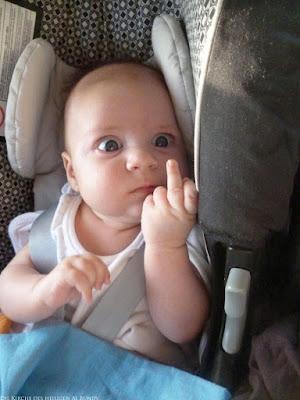 Komisches Baby zeigt Stinkefinger - lustiges Foto im Kindersitz
