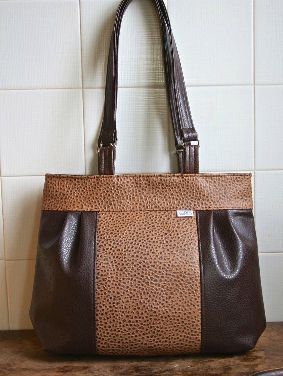 799a28f27340 The exterior of this bag is made completely from faux leather. I used 2  coordinating patterns  one solid pebbled chocolate brown for the pleated  sides and a ...