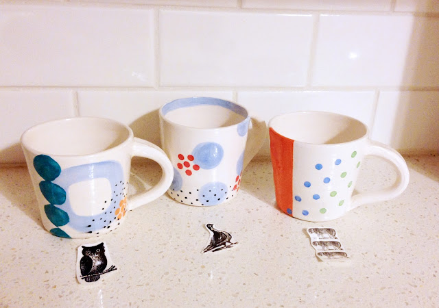 ceramic mugs with decals laid out in front
