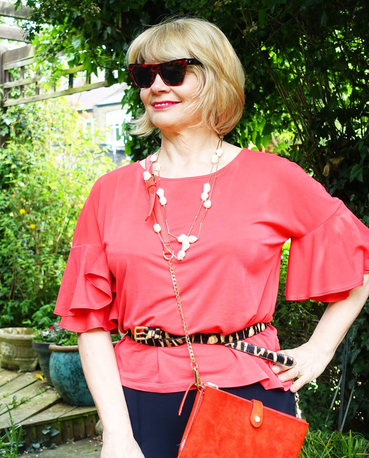 Woman wearing red square sunglasses and red top with statement sleeves