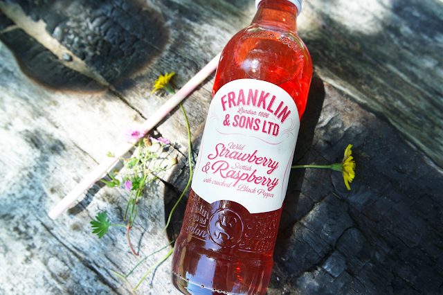 a glass bottle filled with red strawberry and raspberry soda propped on a piece of wood