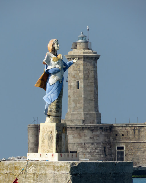 The statue of the Madonna dei Popoli (Our Lady of the Peoples) and the lighthouse at the south end of the Diga Curvilinea (Curvilinear Breakwater), port of Livorno