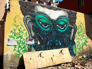 Street art by Yantr showing Buddha wearing an out-of-this-world mask