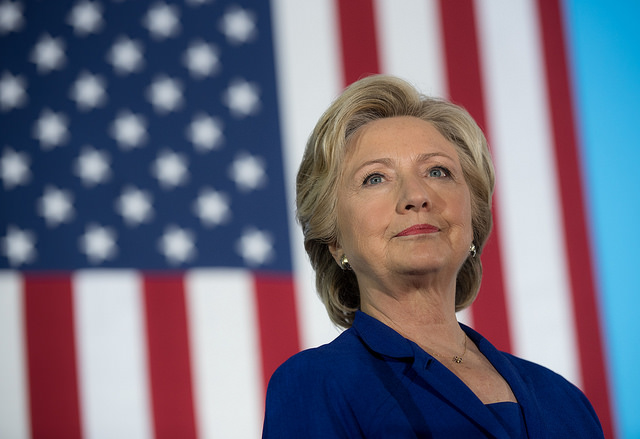 image of Hillary Clinton in a blue pantsuit, standing in front of a US flag