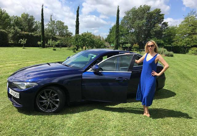 Blondes Model steht neben Aöfa Romeo Giulia auf grünem Rasen mit Hosenanzug von American Vintage in Blau