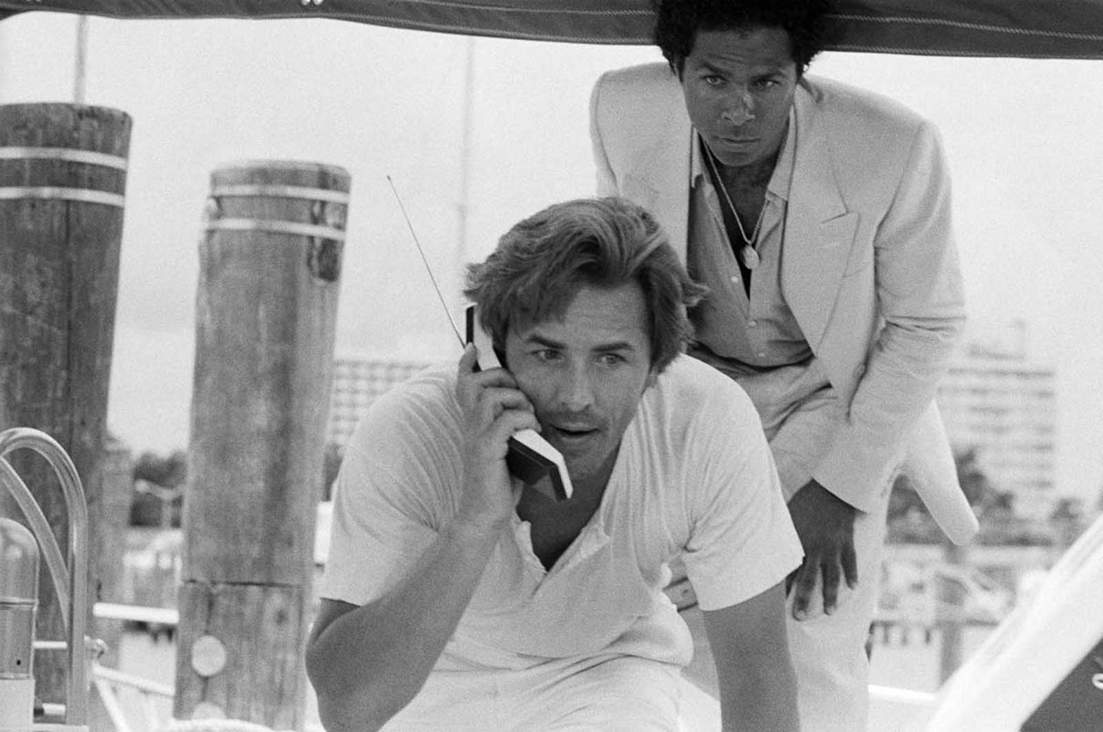 "Don Johnson como detetive James ""Sonny"" Crockett e Philip Michael Thomas como detetive Ricardo ""Rico"" Tubbs - e um telefone celular. 1984."
