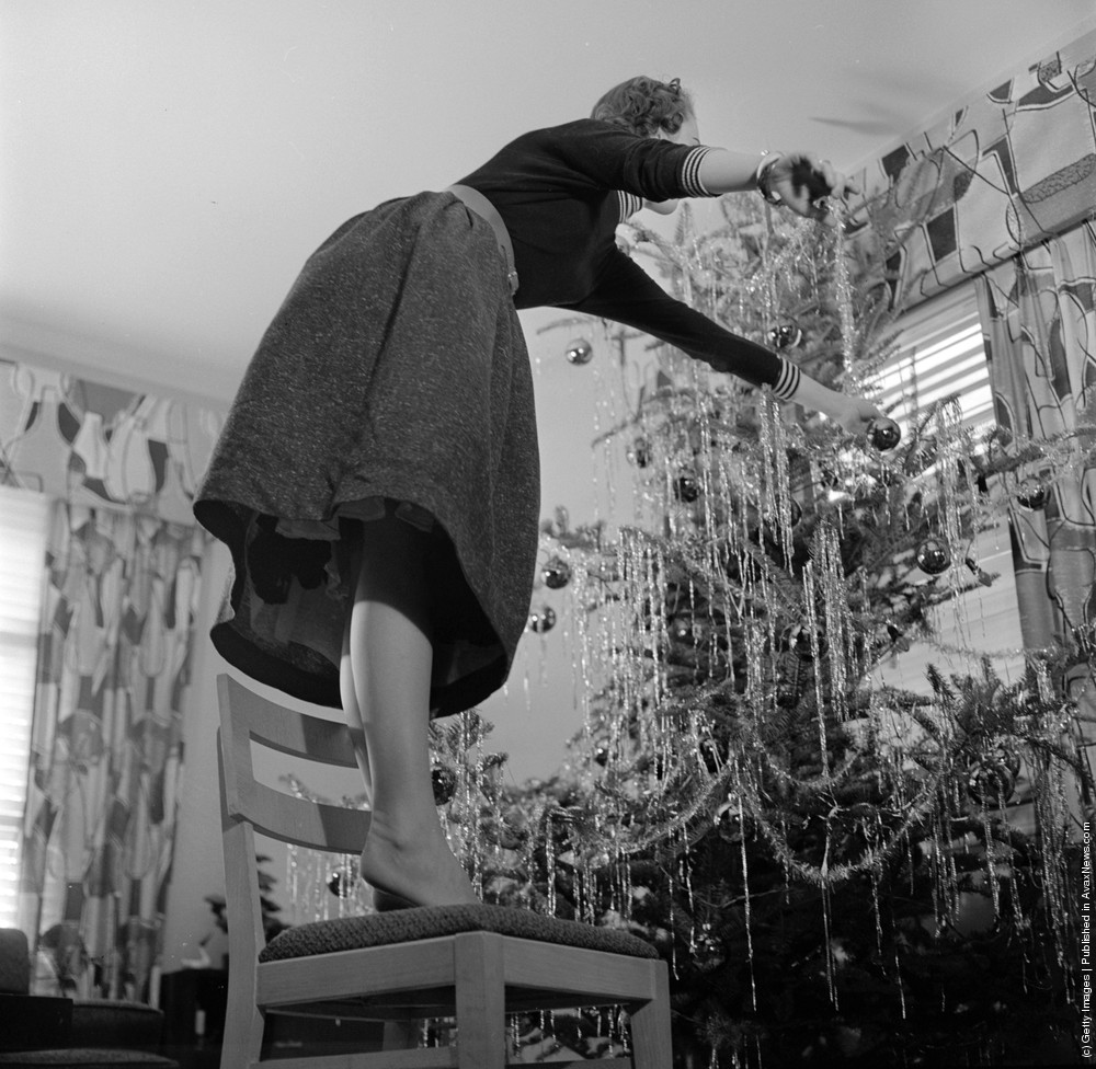 When Decorating A Christmas Tree Use Firm Stepladder And Dont Be Like This Woman Who Is Standing On Chair Leaning Over Too Far Circa 1955 Photo