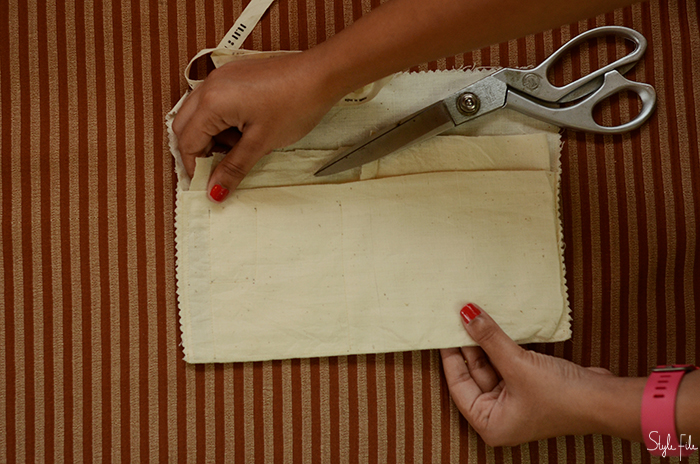 An image of canvas cloth being measured by a woman with orange nails and a pink FitBit for a do-it-yourself mini crossbody sling bag project on Style File