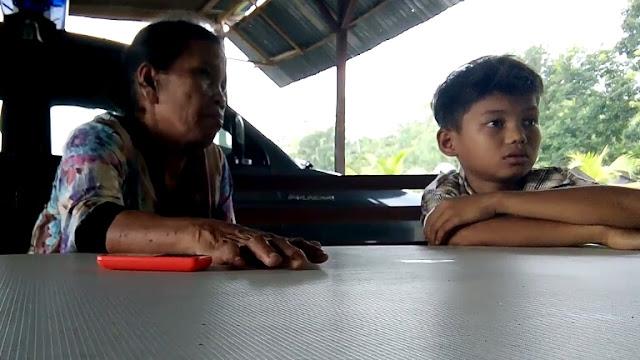 Boru Manurung saat menemani anak bungsu korban di Mapolsek Kota Kisaran untuk dimintai keterangannya sebagai saksi.