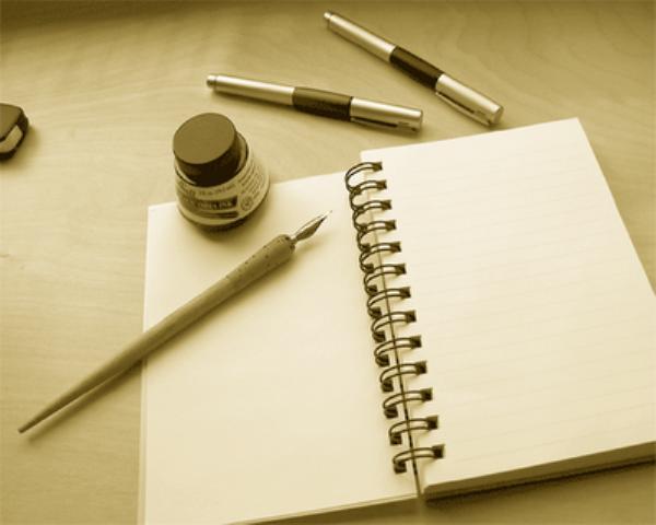 Imagen de cuaderno y pluma para escribir