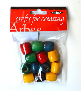 "Packet of wooden beads in solid colours: red (2), green (3), yellow (4) and blue (4). The brand is ""Arbee""."