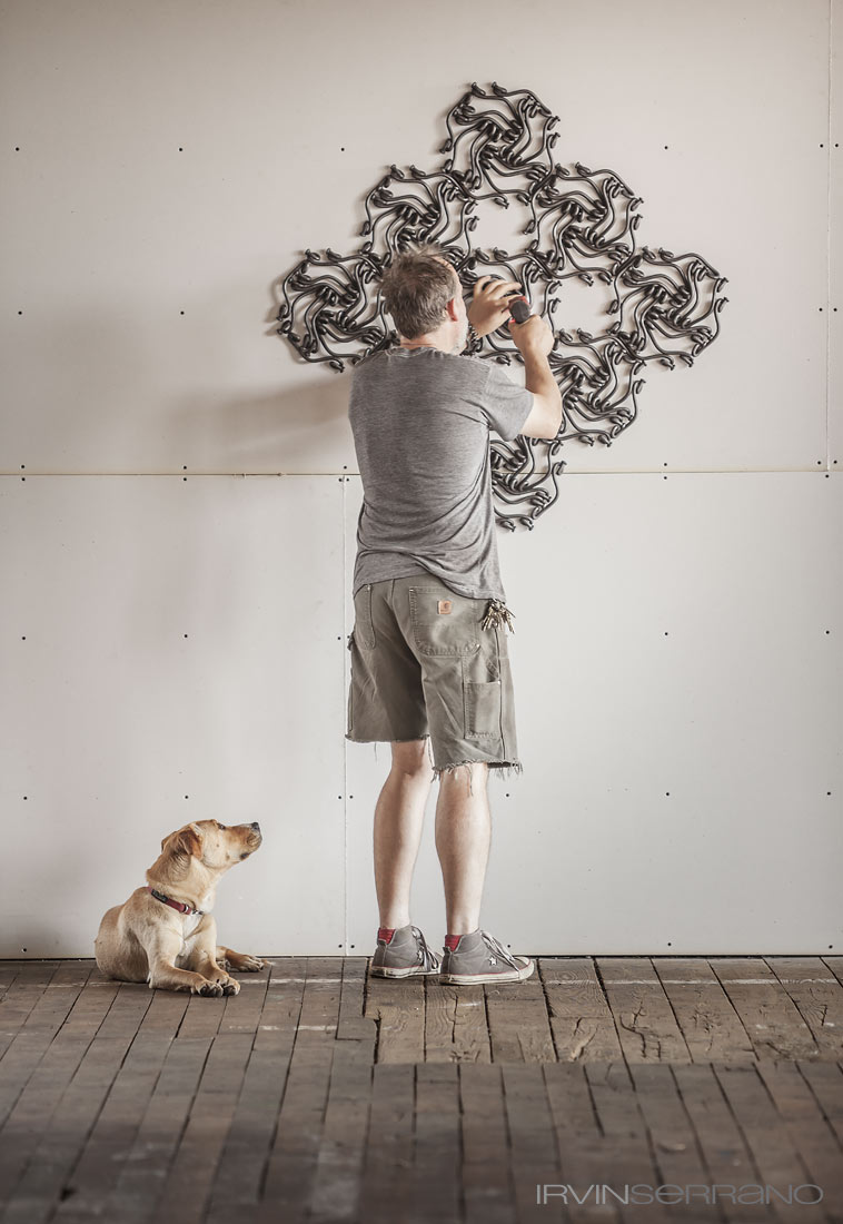 His dog looks on as John Bisbee hangs a sculpture on the wall in his Brunswick studio in Maine.