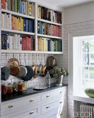 kitchen with bookshelf with colorful books, white subway tiles and black countertops via elle decor and belle vivir blog