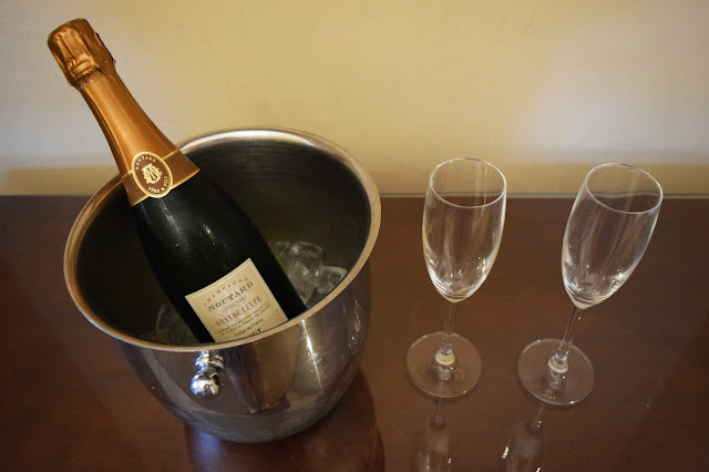 A bottle of Champagne inside a cooler with two champagne glasses beside it