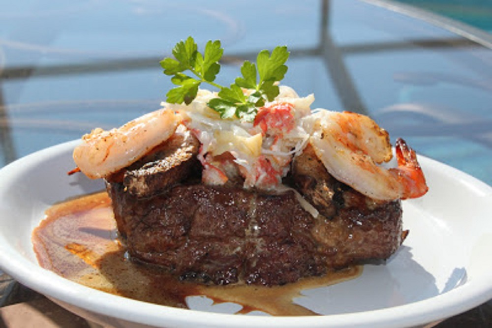 this is a grilled filet mignon piece of beef with shrimp , crab and wine sauce on top
