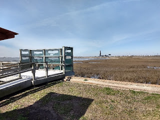 boardwalk leading to a platform with a screen wall overlooking a salt marsh