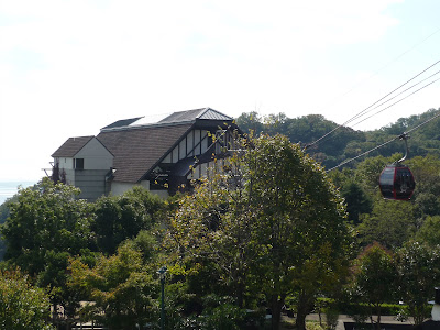 Middle ropeway station of the Shin-Kobe ropeway as seen from above in the Nunobiki herb garden, Kobe. A ropeway gondola is visible on the right side of the frame, a little sliver of ocean in the distance on the left