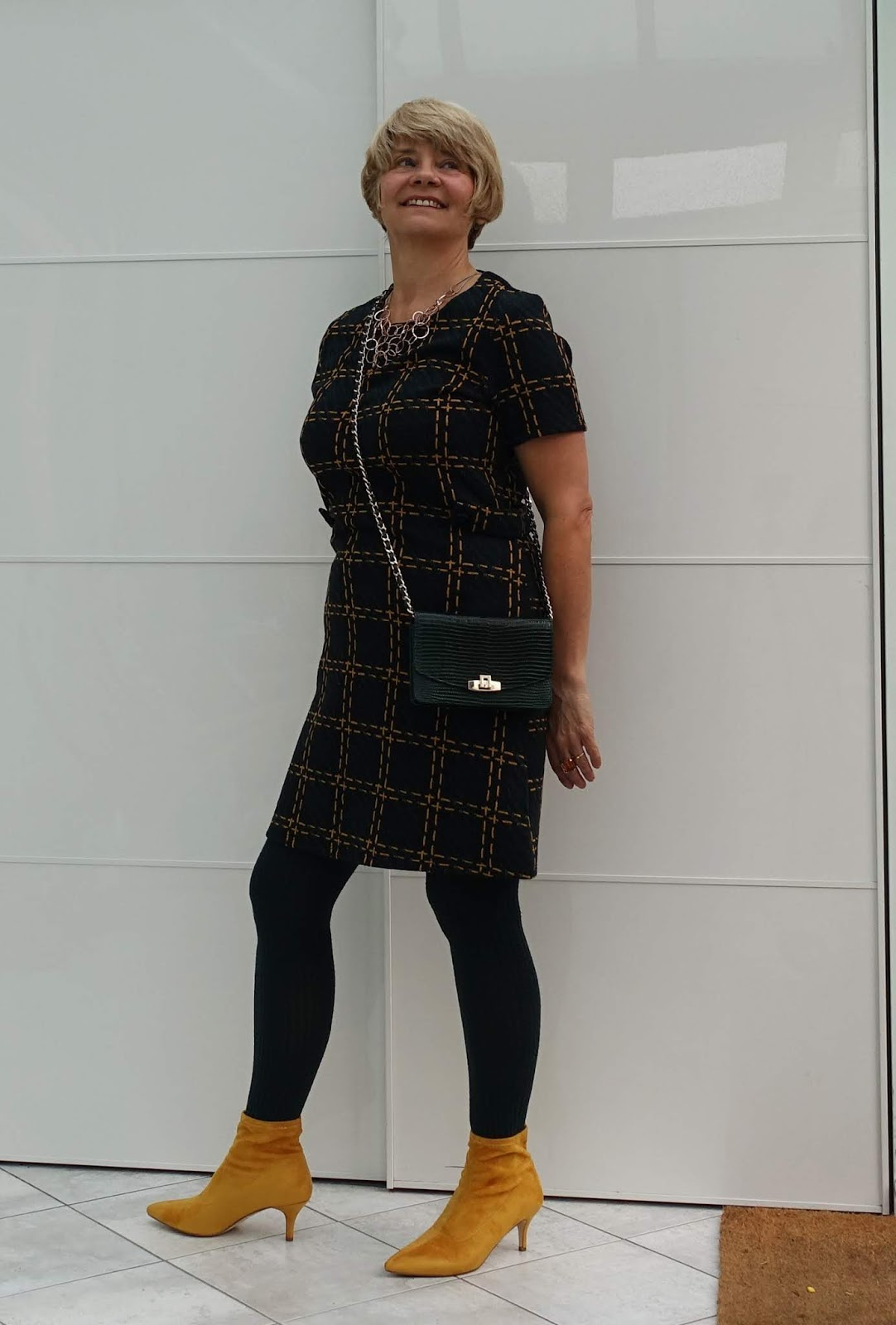 Over 45 year old woman in knee length forest green and mustard stripe dress, cross-the-body-bag and mustard ankle boots in a look for AW18