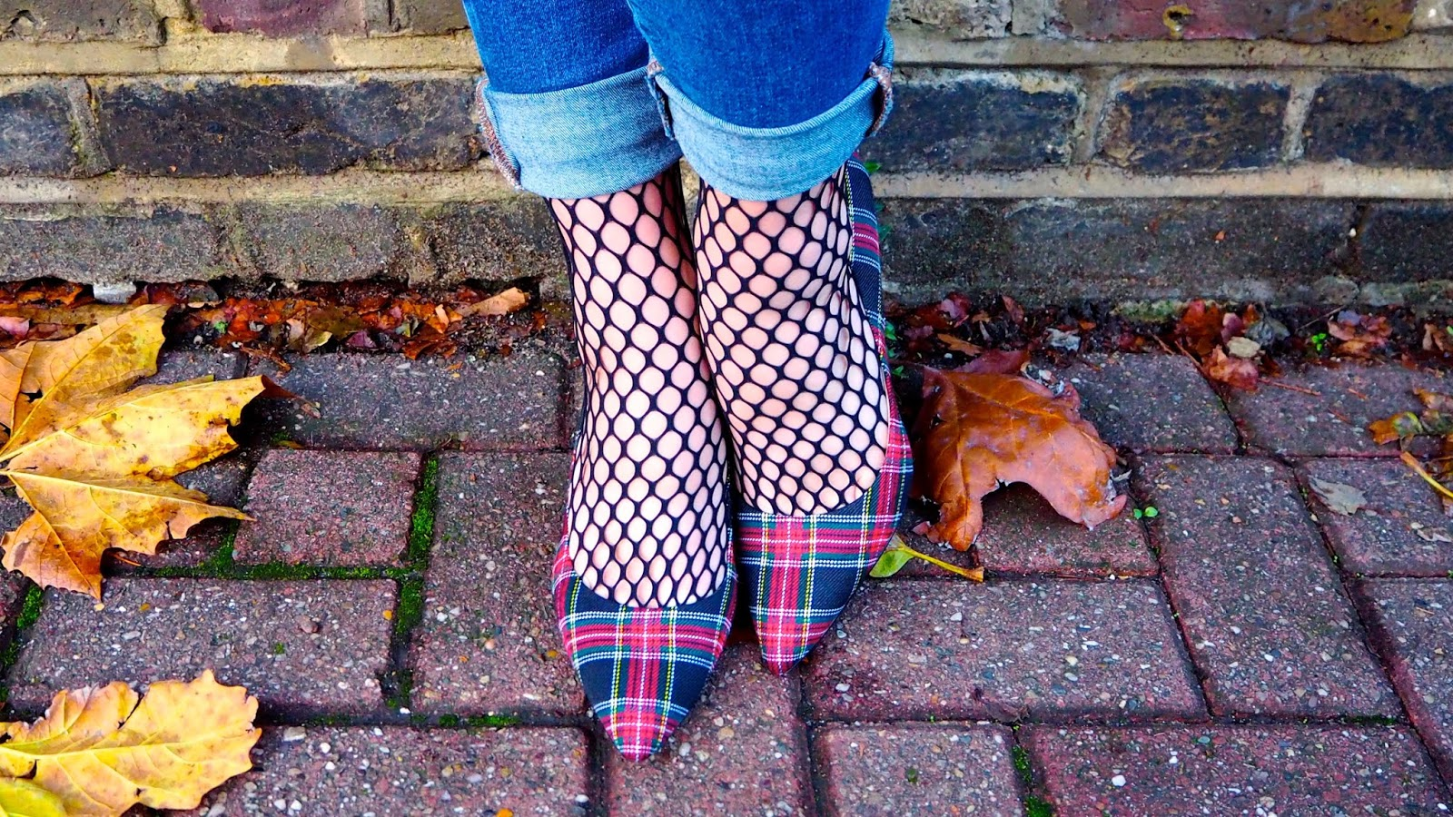 rolled up jeans, oversized fishnet socks, red plaid pointed toe high heels and autumn leaves on the ground