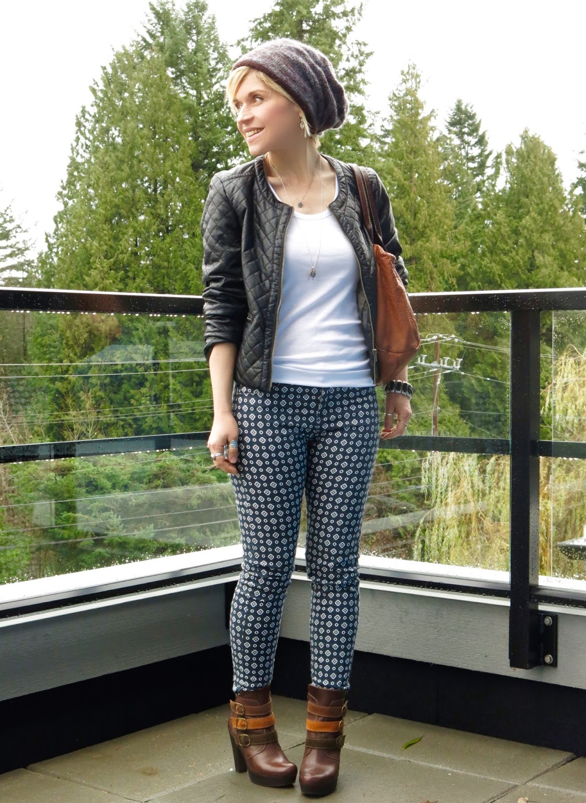 styling printed skinny pants with a white tank, quilted faux-leather jacket, platform booties, and a woolen beanie