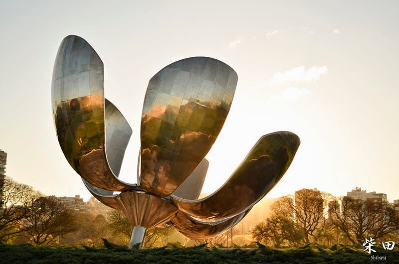 The sculpture is located in the center of a park of four acres of wooded boundaries, surrounded by paths that get closer and provide different perspectives of the monument, and placed above a reflecting pool, which apart from fulfilling its aesthetic function, protects it. It represents a large flower made of stainless steel with aluminum skeleton and reinforced concrete, which looks at the sky, extending to it its six petals.