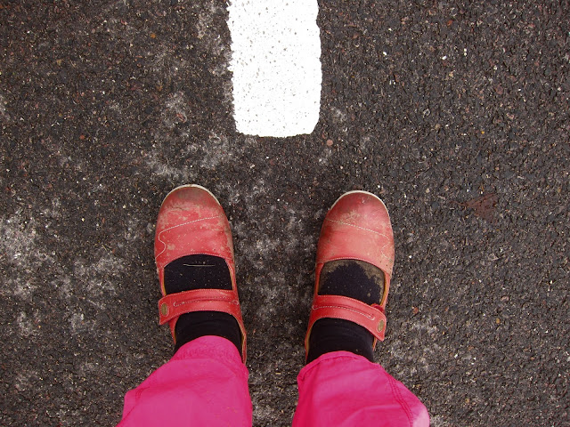 Red shoes, pink trousers, black tarmac, white line