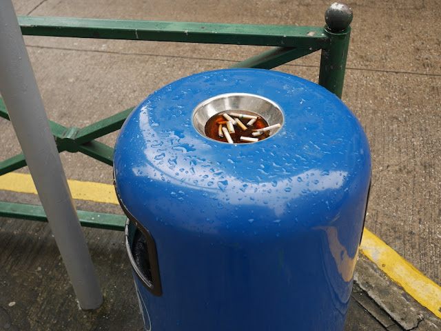 trash can with ashtray on top filled with cigarette butts and water in Macau