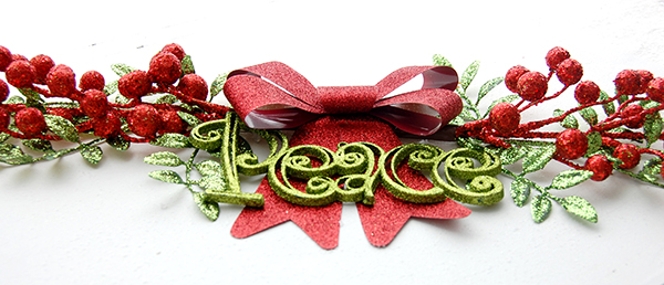 red and green picks, green peace ornament, red glitter ribbon upclose