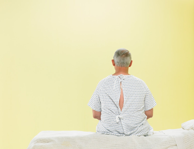 An older man sitting on a hospital bed