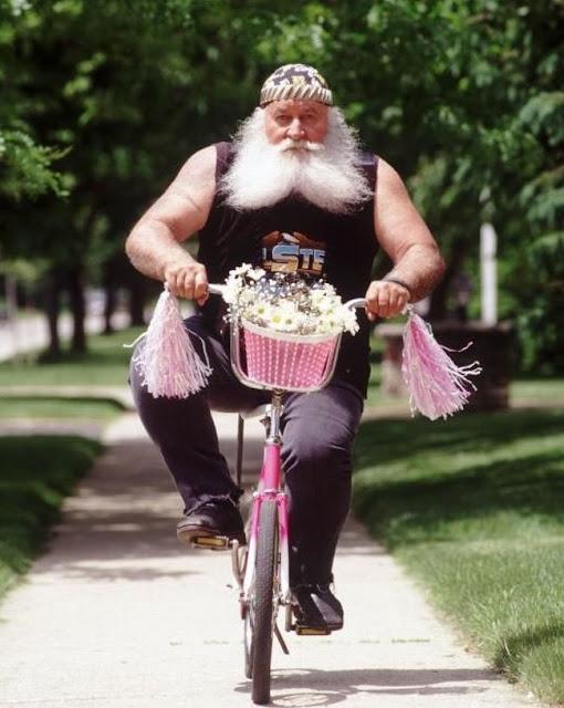 O contraste de um cara forte e robusto com a bicicleta rosa de sua neta é um pouco desconcertante