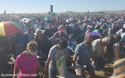 Miles de cristianos orando de rodillas tomados de la mano en Sudáfrica.