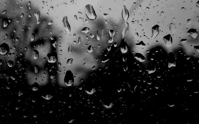 Slecht weer met regendruppels op het raam