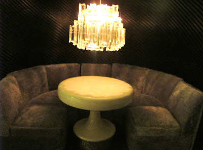 Modern one-twelfth scale miniature nightclub scene of a curved booth is grey velvet, with a round table in the middle and a large crystal chandelier hanging above it.