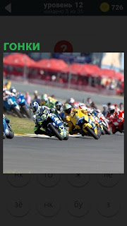 По треку начались гонки на мотоциклах, входят в поворот участники