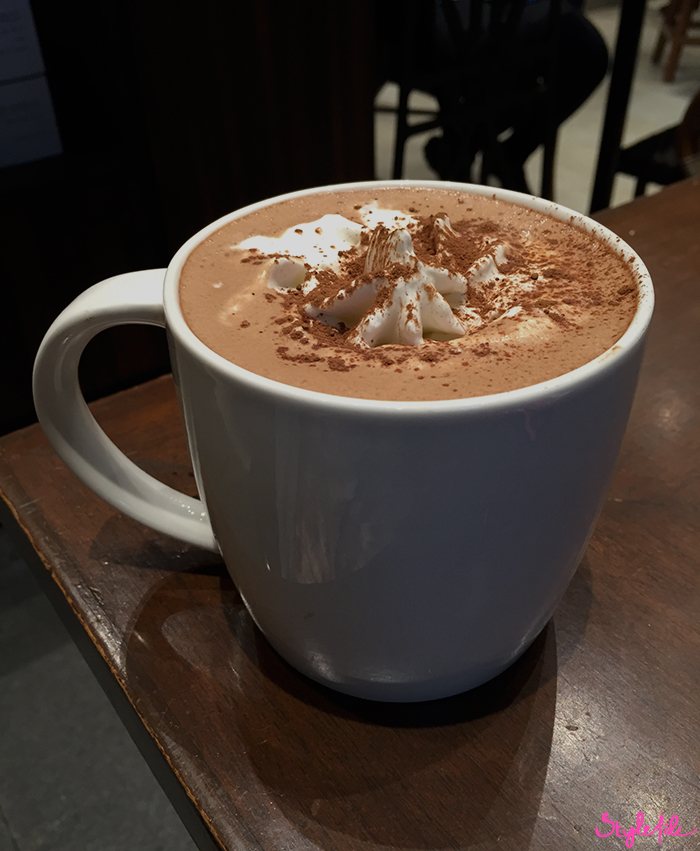 An image of a white Starbucks coffee mug filled with hot chocolate topped with foam, whipped cream and cocoa on a wooden table at Starbucks India