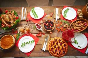 Don't show up hungry Some people think that by starving themselves before a holiday meal, they will be able to treat themselves at the table to a spectacular meal and compensate for their lack of eating beforehand. This is wrong. If you show up starving, you will just end up eating more than you would have if you ate breakfast.     Use smaller plates Studies have found that people serve themselves in proportion to their plate size. It, therefore, follows that the smaller your plates, the lesser the possibility that you are going to overeat.