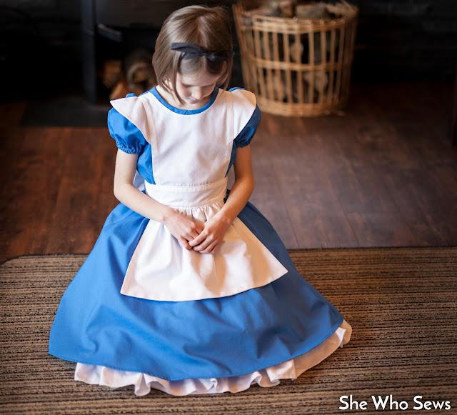 Apron spread over blue dress skirt