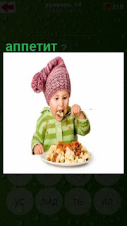 ребенок за столом с хорошим аппетитом ест кашу