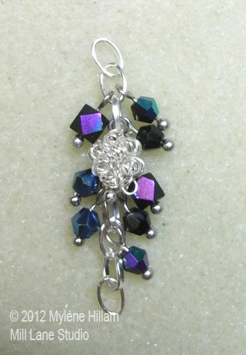 Shiny, coiled wire beads and black bicone beads with an iris finish dangle in a bunch on a silver chain
