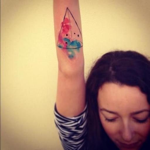Um cone com uma aquarela de difamação é representado na parte inferior do utente do antebraço neste tatuagem.