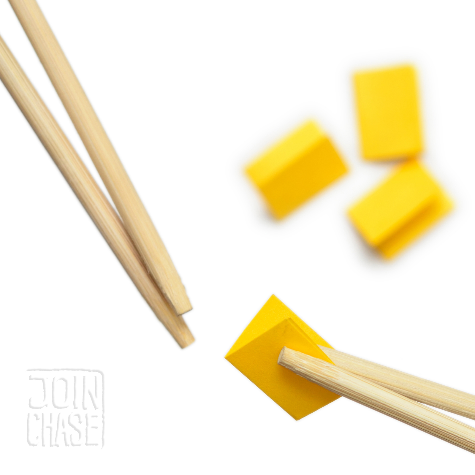 Paper being passed between wooden chopsticks during a game in an English class.