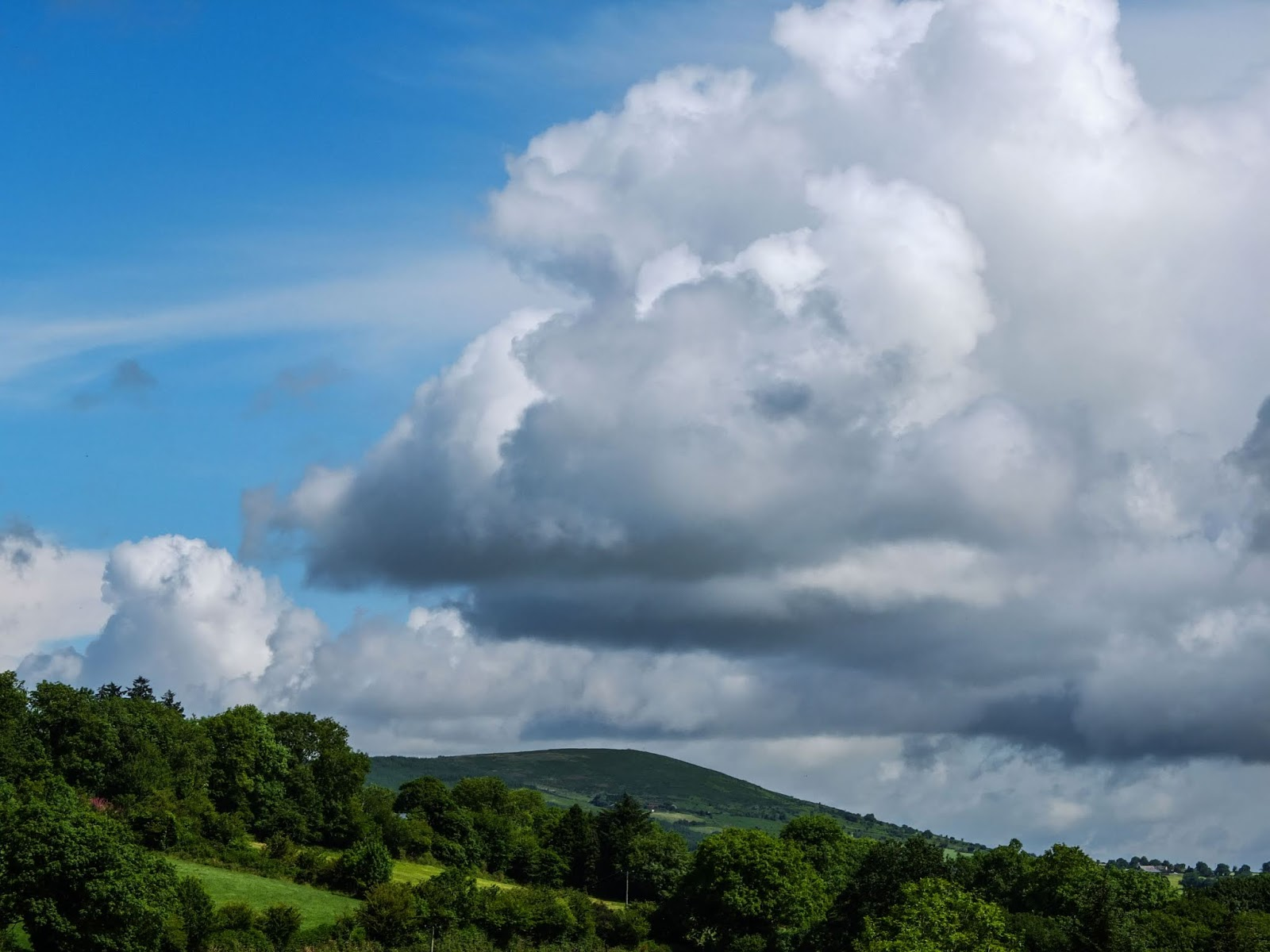 Big, fluffy clouds over a mountain in North Co.Cork.