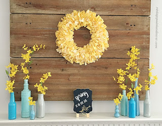 Vintage Paint and more - Spring mantel done with a yellow fabric rag wreath, blue painted bottles with forsythia stems and a cute chalk board