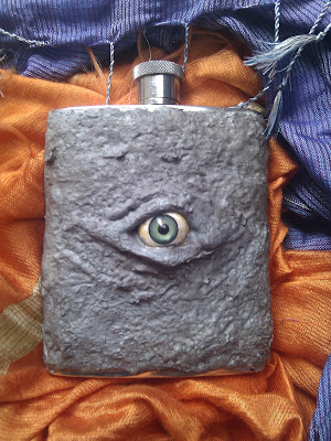 Hip Flask with an evil eye and horrible mottled skin.