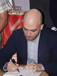 Roberto Saviano signing a copy of  one of his books